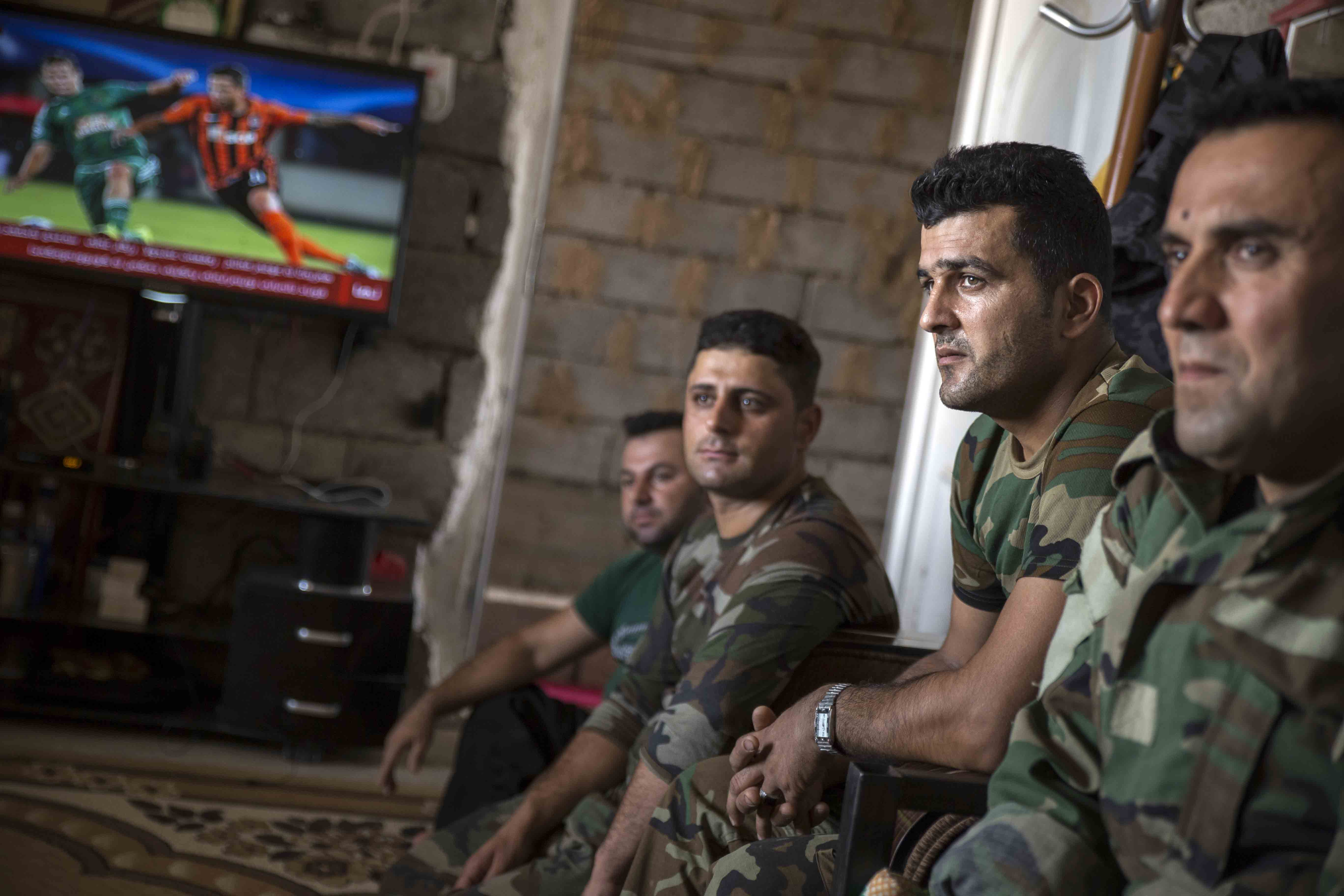 Peshmerga fighters listen to their commander. The house where they sit was captured from Islamic State and is now used as a Peshmerga base.