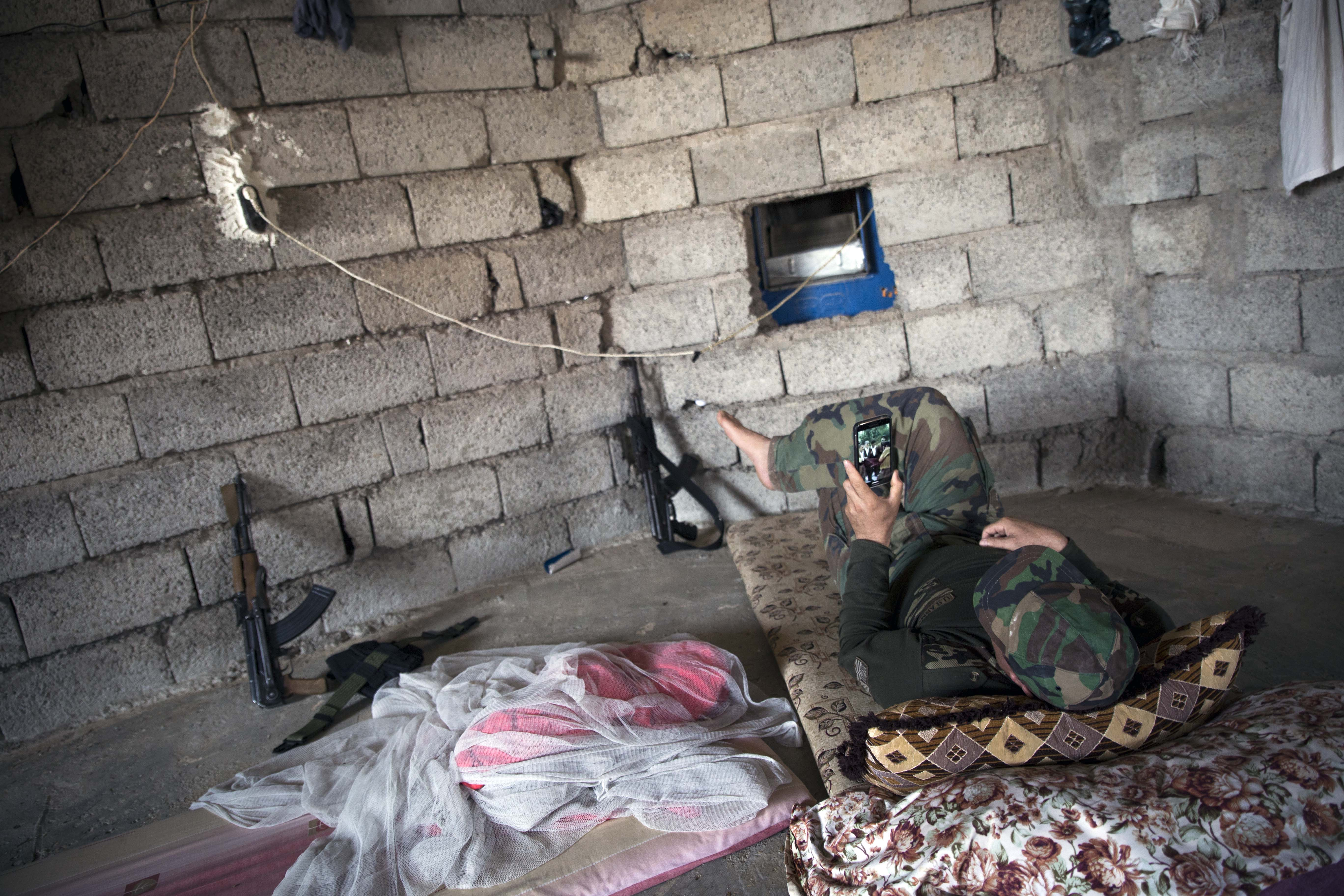 A Peshmerga fighter is using his phone for relaxation. Several fighters said there was not much to do: