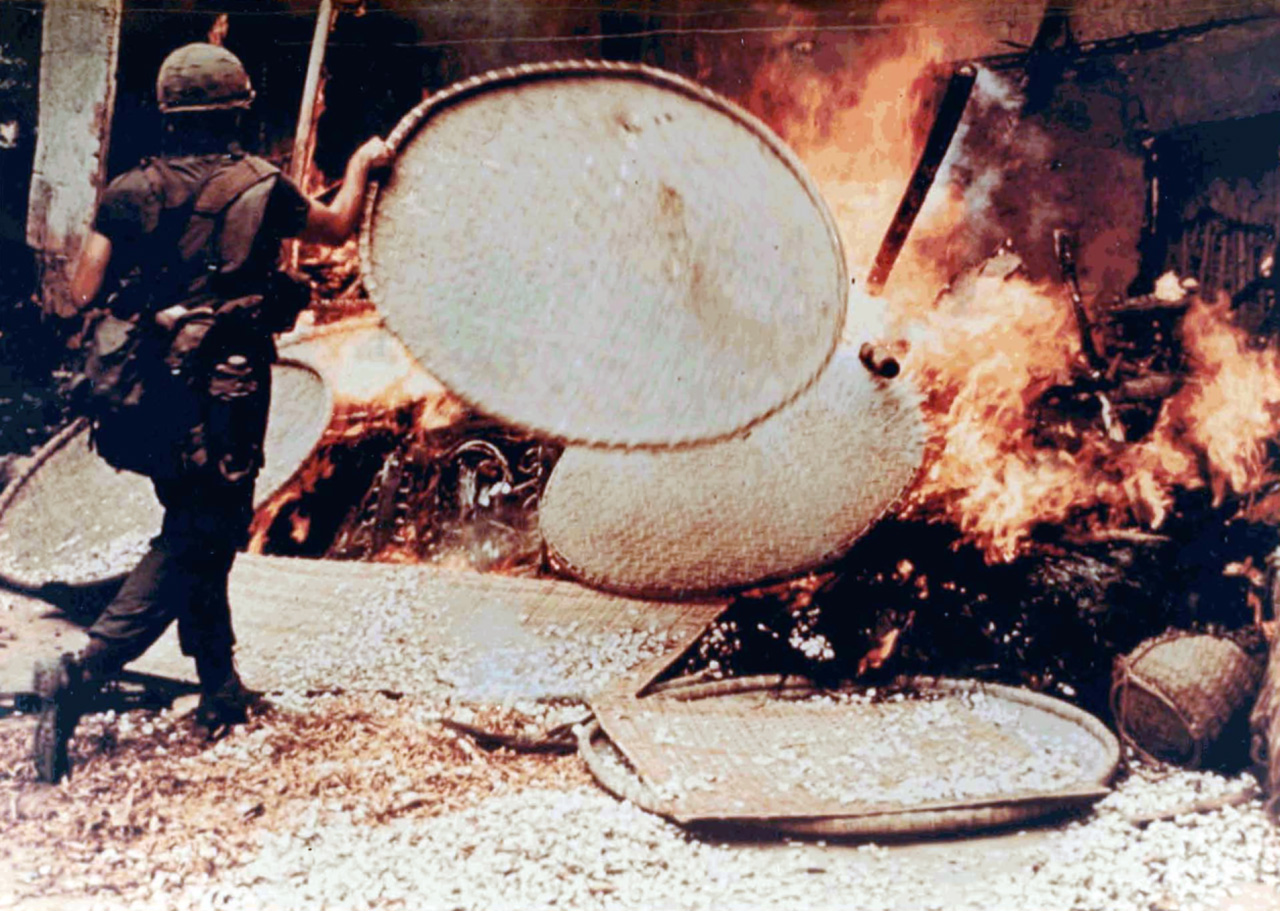 A US soldier burns a Vietnamese dwelling during the My Lai massacre, 1968, when between 350 and 500 unarmed civilians were killed by US soldiers.