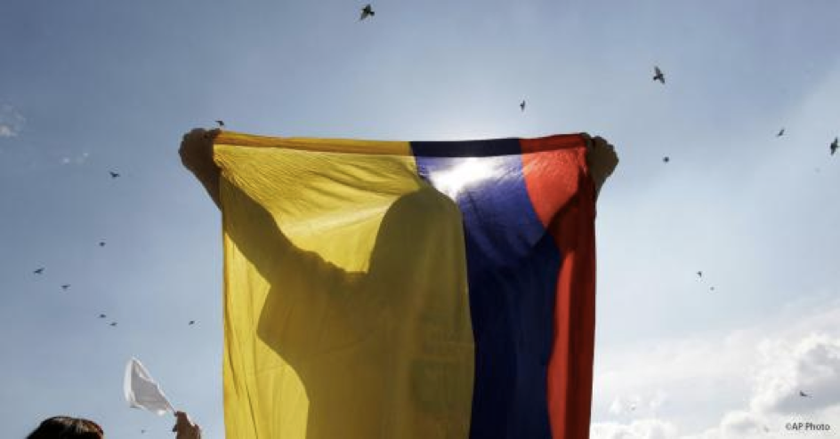 A demonstrator holds the Colombian flag during a march against the Revolutionary Armed Forces of Colombia, or FARC, in Bogota.