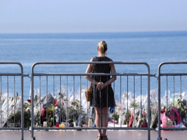 A woman stands by a makeshift memorial in tribute to the victims of the deadly Bastille Day attack at the Promenade des Anglais in Nice (AFP Photo/Valery Hache)