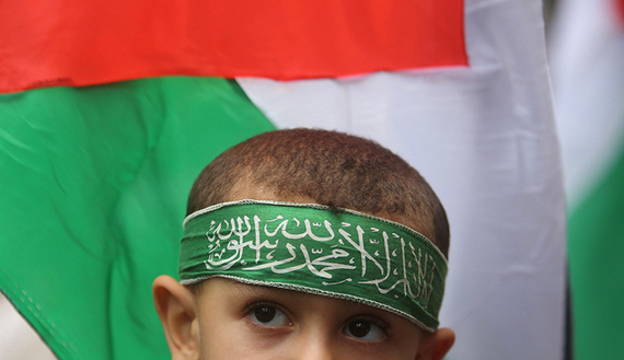 Palestinian boy wears a Hamas headband during an anti-Israel rally, in the central Gaza Strip, Oct. 23, 2015. (photo by REUTERS/Ibraheem Abu Mustafa)