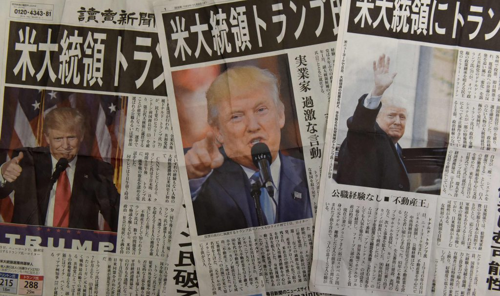 This photo illustration shows extra editions of Japanese newspapers reporting the victory of Donald Trump in the US presidential election in Tokyo on November 9, 2016. AFP PHOTO / TORU YAMANAKA