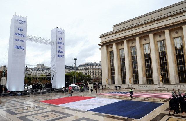 """Parisians unfurled American and French flags at a rainy memorial ceremony where two towers read in French and English respectively, """"Les Français n'oublieront jamais--The French will never forget."""" (Getty image)"""